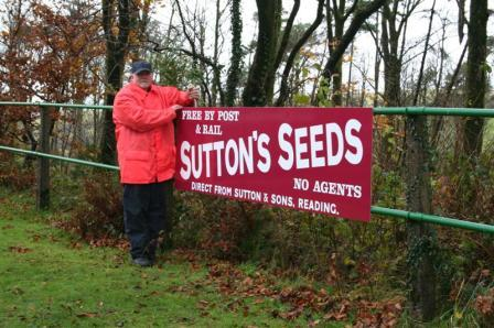 "Jim Pounds installs the ""Sutton Seeds"" sign on the down platform railings."