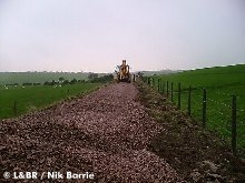 Contractors levelling out ballast near the first farm crossing