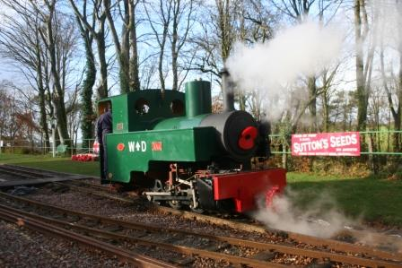 "Axe - steaming past the Garden of Remembrance on the down platform. ""Suttons Seeds"" signs recently produced by Jim Pounds"